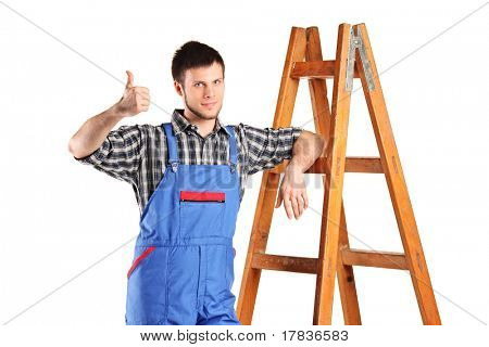 A manual worker standing next to a wooden ladder and giving thumb up isolated on white