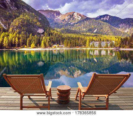 Lake in South Tyrol, Italy. Pair of comfortable sun loungers on the lake. The concept of walking and eco-tourism. Water reflects the surrounding mountains and forest