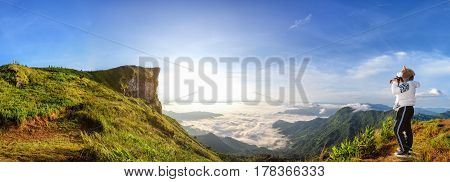 Panorama beautiful landscape nature of sunrise on peak mountain with sun cloud fog bright sky and woman tourist are taking photos in winter at Phu Chi Fa Forest Park is a attraction of Chiang Rai Province Thailand