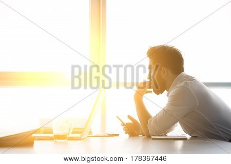 Toned of businessman waiting for interview while sitting at table and looking at window. Handsome man having stress before interview.