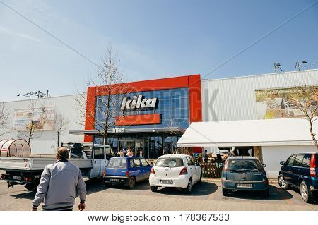 BUCHAREST, ROMANIA - APR 1, 2016: Man walking toward Kika entrance facade of the furniture and household store. Kika is an international chain of furniture stores, headquartered in Austria.