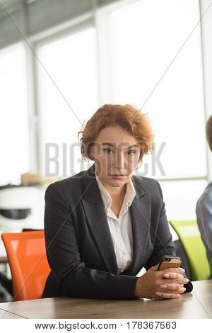 Angry business woman sitting at table in office and she is going to take interview. Aggressive lady looking at camera and looking strange for new workers.