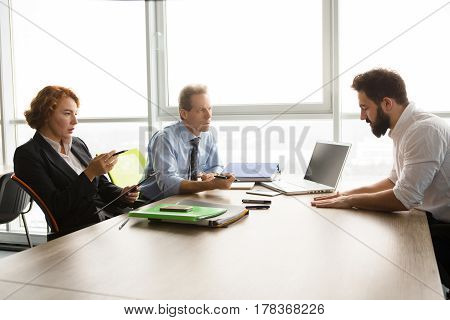Business or freelance concept. Business people taking interview while sitting at table in office. Business representatives man and woman communicating with new worker.