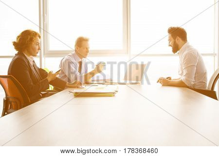 Toned of job interviewer giving his CV to be admitted to huge company, firm, enterprise. Handsome man communicating with employees in board room in office.