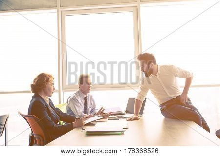 Toned of handsome man communicating with employees in board room in office. Job interviewer man offering his CV to be admitted to huge company, firm, enterprise.