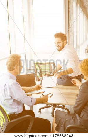 Toned of handsome businessman sitting on table in office and giving his CV to employees. Business people taking interview in board room.