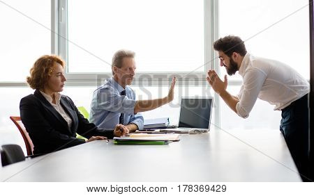Toned of bearded Indian man bowing in front of employees and asking them to give him job position in company. Handsome man clasped his hands.
