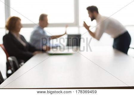 Closeup of bare table in board room in office. Handsome Indian man asking employees to give him place in their company.