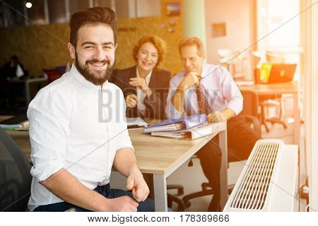 Happy entrepreneur man smiling after successful deal with huge company, firm, enterprise. His business colleagues sitting on background in office.