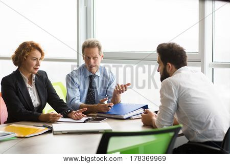 Boss with his colleague communicating with their worker from office. People do not believe him. They condemning their behavior.
