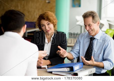 Happy business partners communicating with young man concerning business projects, strategies, etc. Business negotiations concept.