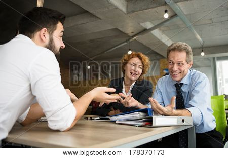 Young business man having interview in office of huge company, enterprise, firm. Business people asking several questions their future worker.