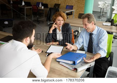 Business people asking several questions their future worker. Young business man having interview in office of huge company, enterprise, firm.