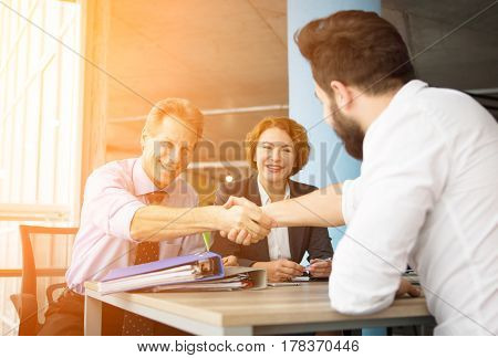 Toned of happy employees congratulating their future worker by shaking hands. Happy people ready to work all together to achieve their goal.