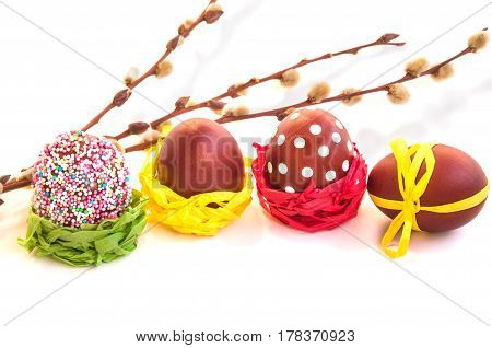 Easter composition with colored eggs and willow branches over white background. Main colors: yellow red green white. Horizontal copy space.