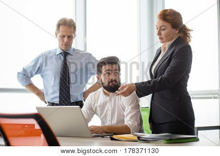 Mobbing, stress, work, scandal concepts. Angry boss lady showing her worker something on laptop computer while staying in board room in office.