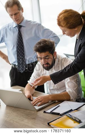 Mobbing, stress, work, scandal concepts. Angry boss lady screaming and shouting at her executive worker while he is using laptop computer for business purposes.