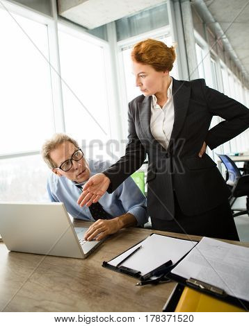 Mobbing, stress, work, scandal concepts. Angry boss woman pointing to laptop computer. Frustrated and disappointed man having stress in office.