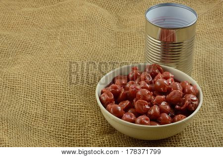 Canned tart pitted cherries in water in white bowl with can