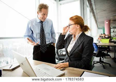 Angry boss man of middle age screaming and shouting at his secretary while she is working on laptop computer in office. Mobbing, stress, work, scandal concepts.