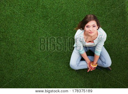 Beautiful young woman sitting on the green grass