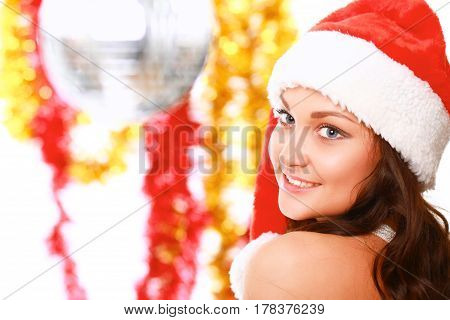 Beautiful girl in santa hat near christmas tree, decorated background.