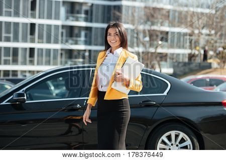 Portrait of a smiling brunette business woman with laptop standing at her car