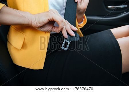 Close up image of business woman sitting in a car putting on her seat belt