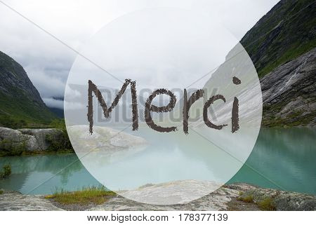 French Text Merci Means Thank You. Lake With Mountains In Norway, Cloudy Sky, Peaceful Scenic Landscape With Rocks And Grass. Greeting Card.