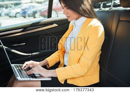 Cropped image of business woman traveling to work in a car checking her emails on laptop