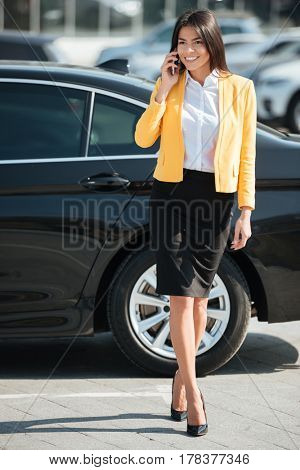 Full length portrait of a beautiful smiling business woman walking away from her car outdoors