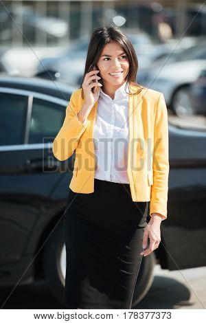 Portrait of a pretty young business woman in smart clothes talking on mobile phone outdoors