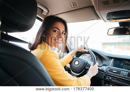 Back view of an attractive young business woman looking over her shoulder while driving a car