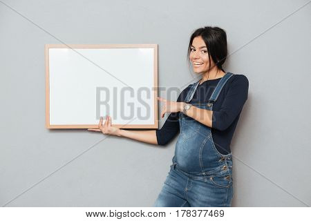 Picture of pregnant happy woman standing and posing while showing copyspace blank over grey background. Looking at camera and pointing.