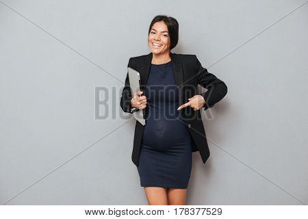 Picture of cheerful pregnant business woman standing and posing over grey background while holding laptop computer and pointing. Looking at camera.