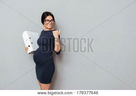 Picture of happy pregnant business woman wearing glasses holding folder standing over grey background and pointing. Looking away.