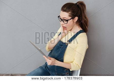 Image of pregnant shocked woman wearing glasses sitting isolated over grey wall while using tablet computer. Looking aside.