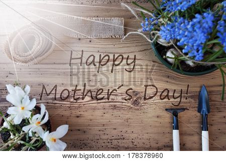 English Text Happy Mother's Day. Sunny Spring Flowers Grape Hyacinth And Crocus, Gardening Tools Like Rake And Shovel, Hemp Fabric Ribbon on Aged Wooden Background.