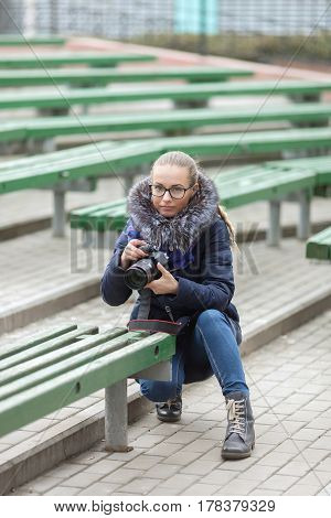 Cute Young Woman With Professional Dslr Camera Taking Pictures Squatting In Spring City Park Outdoor