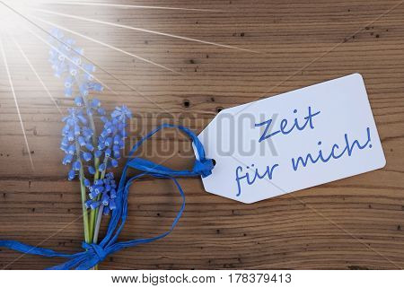 Label With German Text Zeit Fuer Mich Means Time For Me. Sunny Blue Spring Grape Hyacinth With Ribbon. Aged, Rustic Wooden Background. Greeting Card For Spring Season