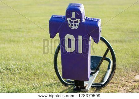 purple tackling dummy on a practice field