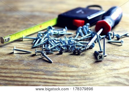 screws and screwdriver stack on old wooden background
