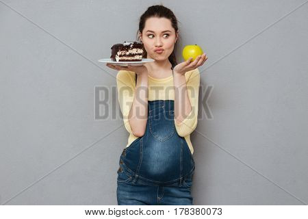 Photo of pregnant lady standing isolated over grey wall while choosing between sweet cake and apple. Looking aside.