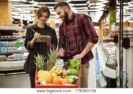 Photo of young cheerful loving couple in supermarket with shopping trolley choosing products. Looking at notebook.