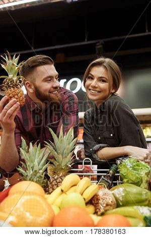 Image of smiling young loving couple in supermarket with shopping trolley choosing fruits. Woman looking at camera.