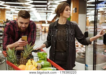 Picture of young cheerful loving couple in supermarket with shopping trolley choosing products. Man looking at mobile phone.