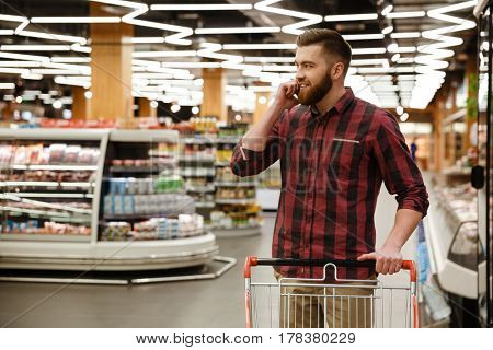 Photo of handsome young man standing in supermarket choosing products while talking by phone. Looking aside.