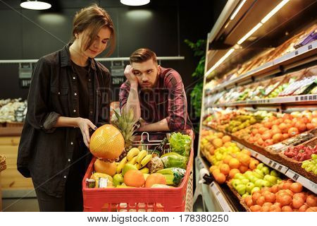 Photo of young loving couple in supermarket with shopping trolley choosing fruits. Tired man looking at woman.