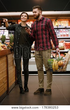 Image of cheerful young loving couple standing in supermarket. Looking aside and pointing.