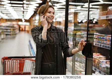 Picture of happy young lady standing in supermarket choosing products while talking by phone. Looking aside.